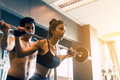 Personal trainer helping women and handle heavy barbells two han Royalty Free Stock Photo