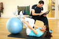 Personal trainer instructing woman in gymnastics Royalty Free Stock Image