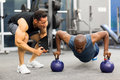 Personal trainer motivates client doing push ups in gym Stock Images
