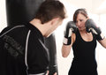 Personal trainer on punch bag woman working out with in gym Royalty Free Stock Image