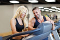 Personal trainer set difficulty on treadmill for woman blonde women in gym Royalty Free Stock Image