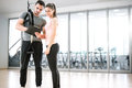 Personal trainer with suspension showing results to client. Royalty Free Stock Photo