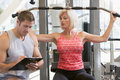 Personal Trainer Watching Woman Weight Train Royalty Free Stock Photography