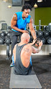 Personal trainer at work with a pupil helping him in passing weights during a situps exercise Stock Photography