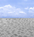 Perspective View of Monotone Gray Brick Stone Street Road. Sidewalk, Pavement Texture Background with Blue Sky and Cloud Royalty Free Stock Photo