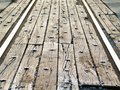 Perspective view of rail road tracks street crossing with old wood and bolts - selective focus Royalty Free Stock Photo