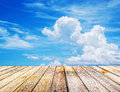 Perspective view to sparse white clouds in the blue sky and background of wood floor texture Stock Photos