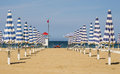 Perspective view of two rows of closed umbrellas at the beginning of the season in rimini the most famous seaside place in italy Royalty Free Stock Image