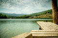 Perspective Wooden board empty table in front of blurred nature background with mountain and lake. Royalty Free Stock Photo