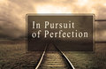 In persuit of perfection road sign with wording dark railroad background Royalty Free Stock Photography