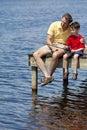 Pesca del padre con il suo figlio su un pilastro Fotografia Stock
