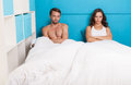 Pessimistic couple having an argument sitting on bed in the Stock Photo