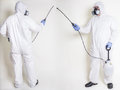 Pest control worker spraying a while dressed in bio hazard coveralls and wearing safety goggles gloves and respirator mask front Royalty Free Stock Images