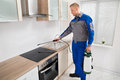 Pest control worker spraying pesticide on induction hob young male in kitchen Royalty Free Stock Photography