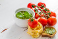 Pesto sauce pasta and tomatoes, white wood background Royalty Free Stock Photo