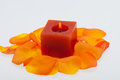 Petals of the orange rose around the candle spilt aromatic Royalty Free Stock Photos
