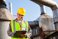 Petrochemical engineer recording smiling senior technical data on clipboard Stock Photo