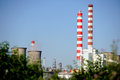 Petrochemical plant seen through green bushes industrial landscape with the Stock Photo