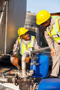Petrochemical wokers inspecting two workers pressure valves on a fuel tank Stock Images
