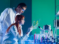 Pharmaceutical scientists studying a sample side view of two young caucasian researchers in laboratory Stock Photos