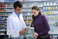 Pharmacist advising client at pharmacy Royalty Free Stock Photo