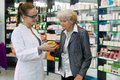 Pharmacist advising medication to senior patient young giving advices about female in a pharmacy Stock Photo