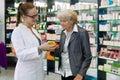 Pharmacist advising medication to senior patient. Royalty Free Stock Photo