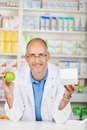 Pharmacist with apple and box showing white in his hands Royalty Free Stock Photography