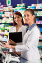 Pharmacist with assistant in pharmacy female standing front of shelf drugs Royalty Free Stock Image