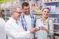 Pharmacist and costumers smiling at pharmacy Royalty Free Stock Images