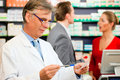Pharmacist with customers in pharmacy Stock Photos