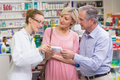 Pharmacist explaining the drug to costumers Royalty Free Stock Photo