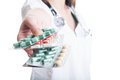 Pharmacist hand offering tablets or blisters with focus on the pills Stock Photos