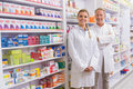 Pharmacist with his trainee standing and smiling at camera in the pharmacy Stock Image