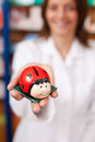 Pharmacist holding ladybird shaped coinbank female at pharmacy Stock Photos