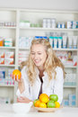 Pharmacist holding orange at pharmacy counter young female Royalty Free Stock Images