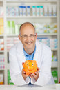 Pharmacist holding piggy bank portrait of smiling mature Stock Images