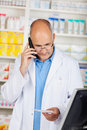 Pharmacist holding prescription paper while using cordless phone mature in pharmacy Royalty Free Stock Images