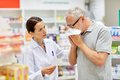 Pharmacist and senior man with flu at pharmacy medicine pharmaceutics health care people concept sick men blowing nose Stock Image