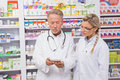 Pharmacist speaking with his trainee about medicine in the pharmacy Royalty Free Stock Photo