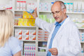 Pharmacist taking out prescribed medicine for customer mature male in pharmacy Royalty Free Stock Image