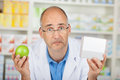 Pharmacist wondering while holding apple and medicine box portrait of male in pharmacy Stock Photo
