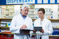 Pharmacists discussing on digital tablet and clipboard Royalty Free Stock Photo