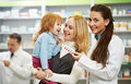 Pharmacy chemist mother and child in drugstore cheerful pharmacist women demonstrating vitamins to girl Royalty Free Stock Images