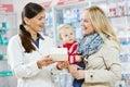 Pharmacy chemist mother and child in drugstore cheerful pharmacist women giving vitamins to girl Stock Photo