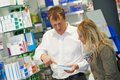 Pharmacy chemist workers in drugstore cheerful pharmacist men worker standing at desk with colleague Stock Images