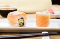 Philadelphia roll sushi on a white plate with soy sauce wasabi and ginger Royalty Free Stock Photo