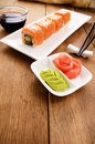 Philadelphia rolls sushi on a white plate with soy sauce wasabi and ginger Stock Photo