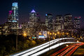 Philadelphia skyline by night on october in the rush hour traffic leaves trails of light on schuylkill expressway Royalty Free Stock Photo