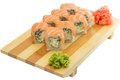 Philadelphia sushi roll on wooden plate isolated on white backgrouns with ginger and wasabi Royalty Free Stock Images
